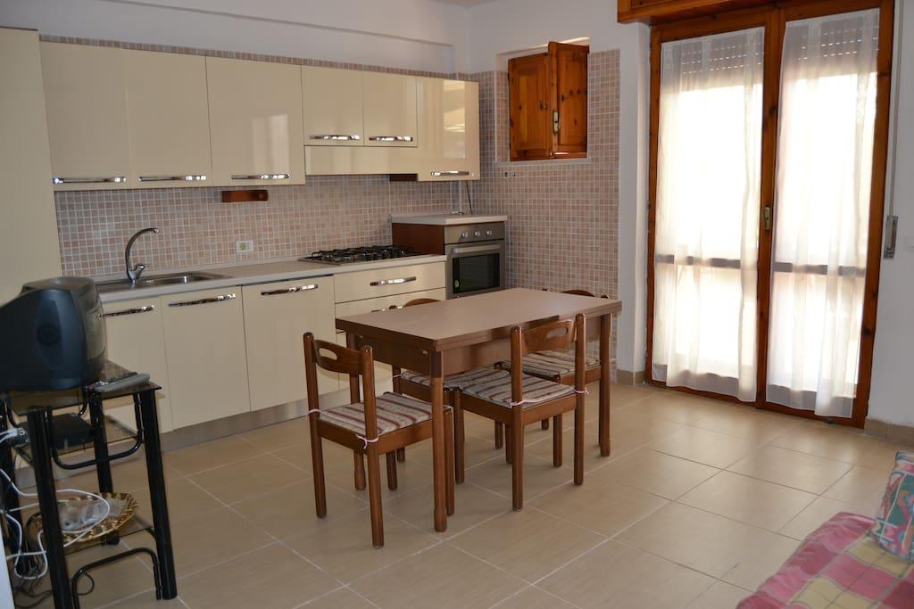 SOGGIORNO/PRANZO. La parete a Cucina è attrezzata con: lavello, piano cottura, forno, frigo, congelatore e lavastoviglie.