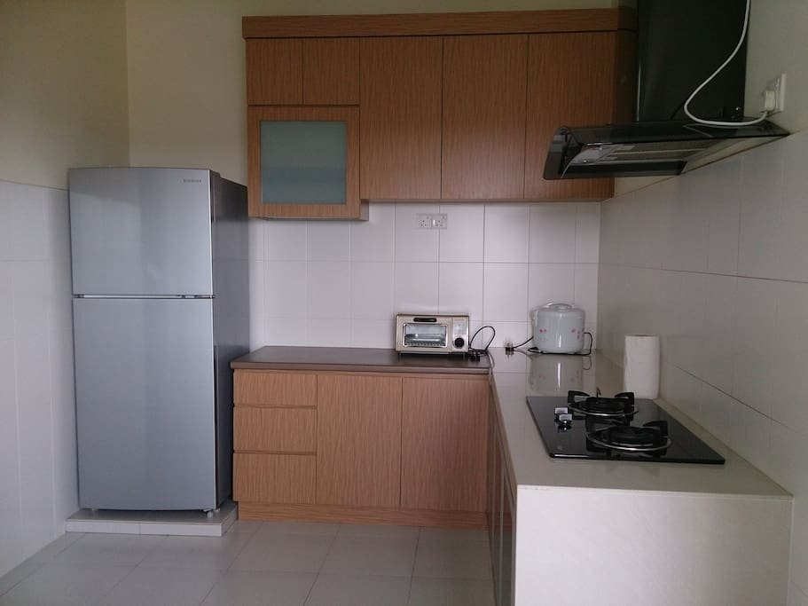 Kitchen with fridge, rice cooker and toaster.