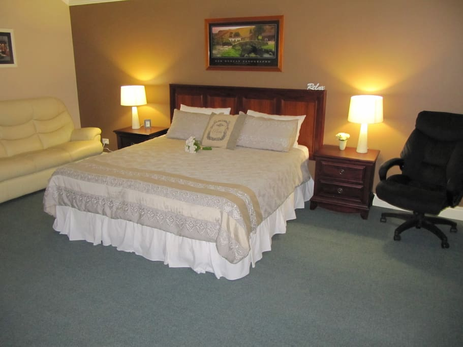 Luxurious air conditioned king bed in a spacious room with bay window and TV/DVD player