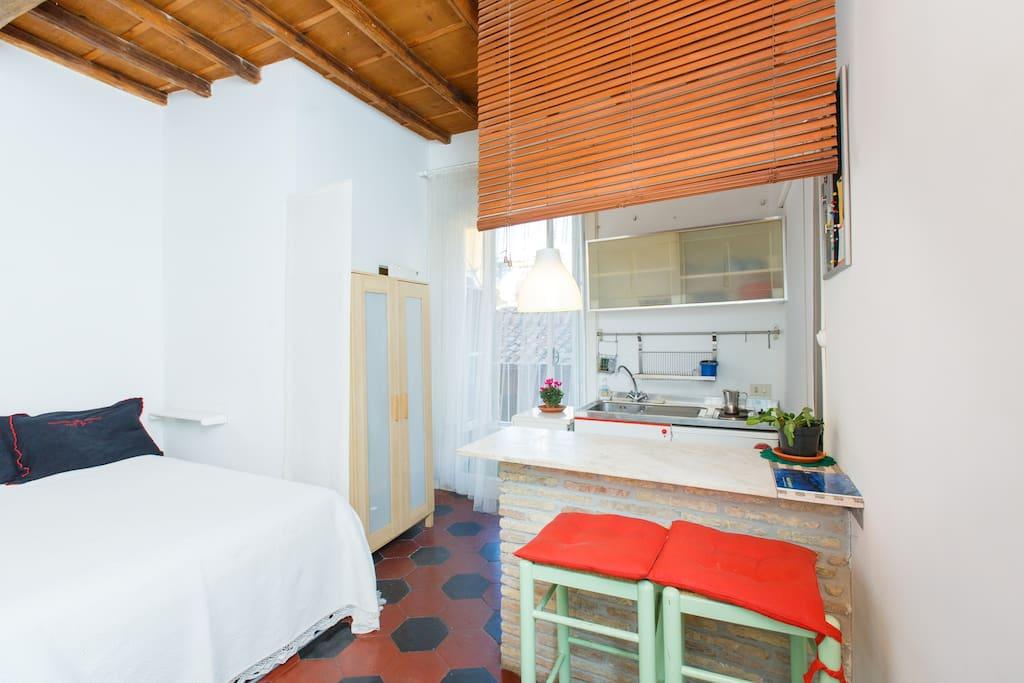 L'angolo cottura, il bancone per mangiare, la finestra e la porta del bagno