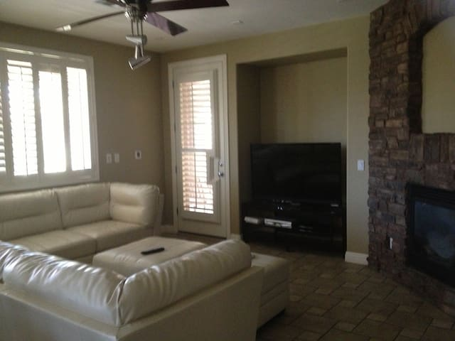Family room with entertainment center, wet bar, and fireplace.