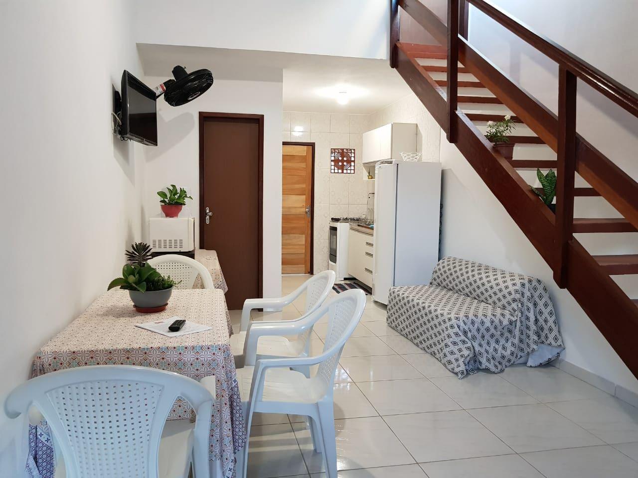 Interior do espaço disponível aos hóspedes. Sala com sofá cama, tv, ventilador, mesas e cadeiras. Wi-fi em todo espaço.