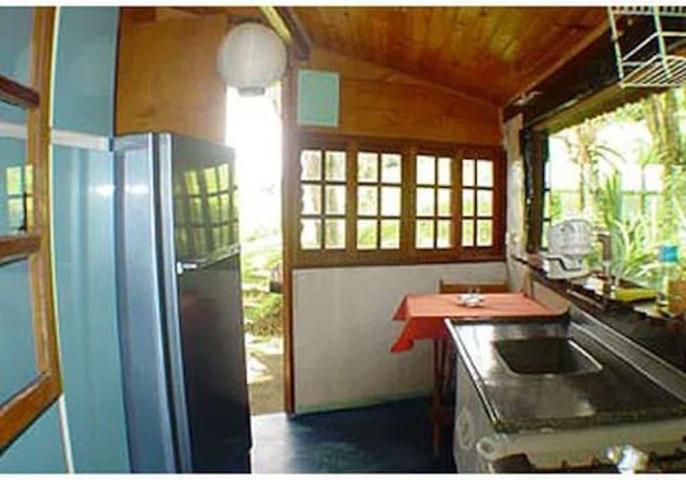 Pequena cozinha com pia, fogão e geladeira.