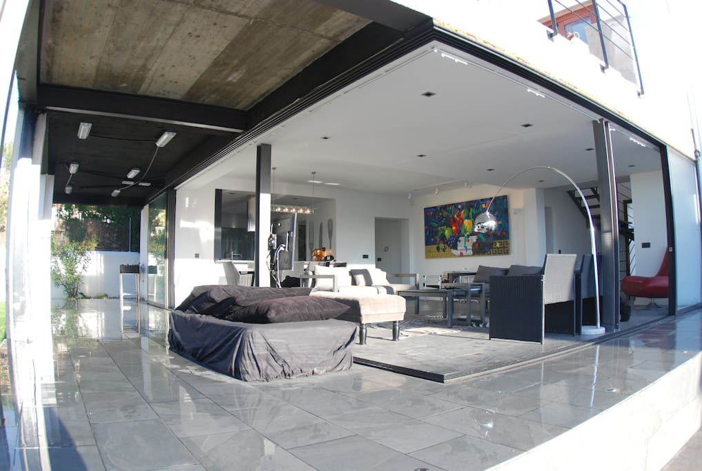 Living/dining area with glass doors fully open.