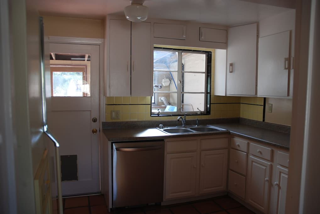 Well stocked kitchen with huge fridge, stainless dishwasher, laundry room through door
