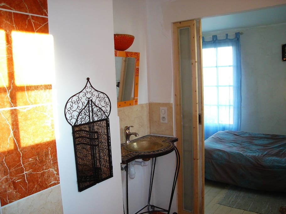 salle d'eau d'inspiration marocaine, avec accès direct à la chambre par une porte coulissante .