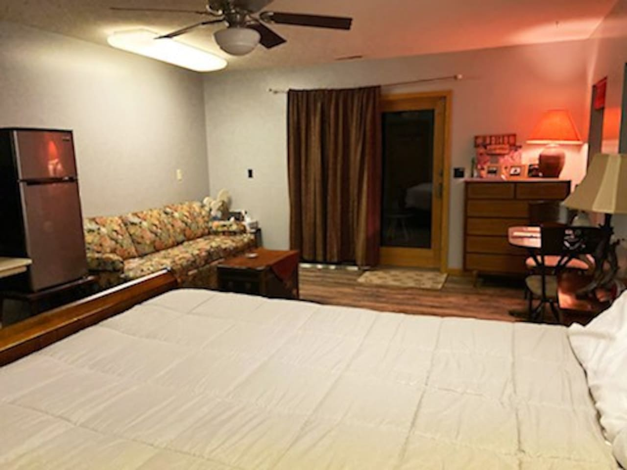 Main guest bedroom w/private entrance, queen size Sleep Number bed, couch refrigerator, microwave, coffee maker, and table for two.