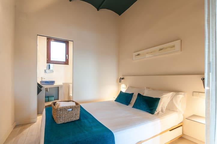cama de matrimonio y acceso directo al baño, focos led de lectura, ambiente de diseño elegante