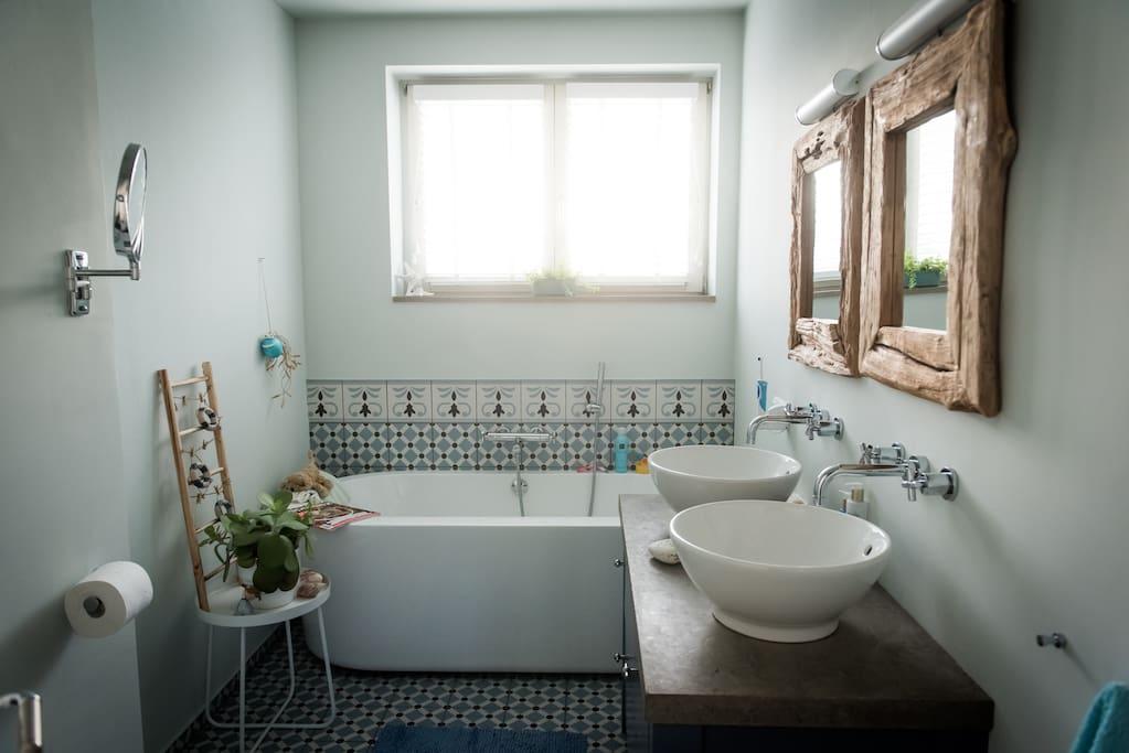 Badkamer met ligbad, dubbel wastafel en toilet