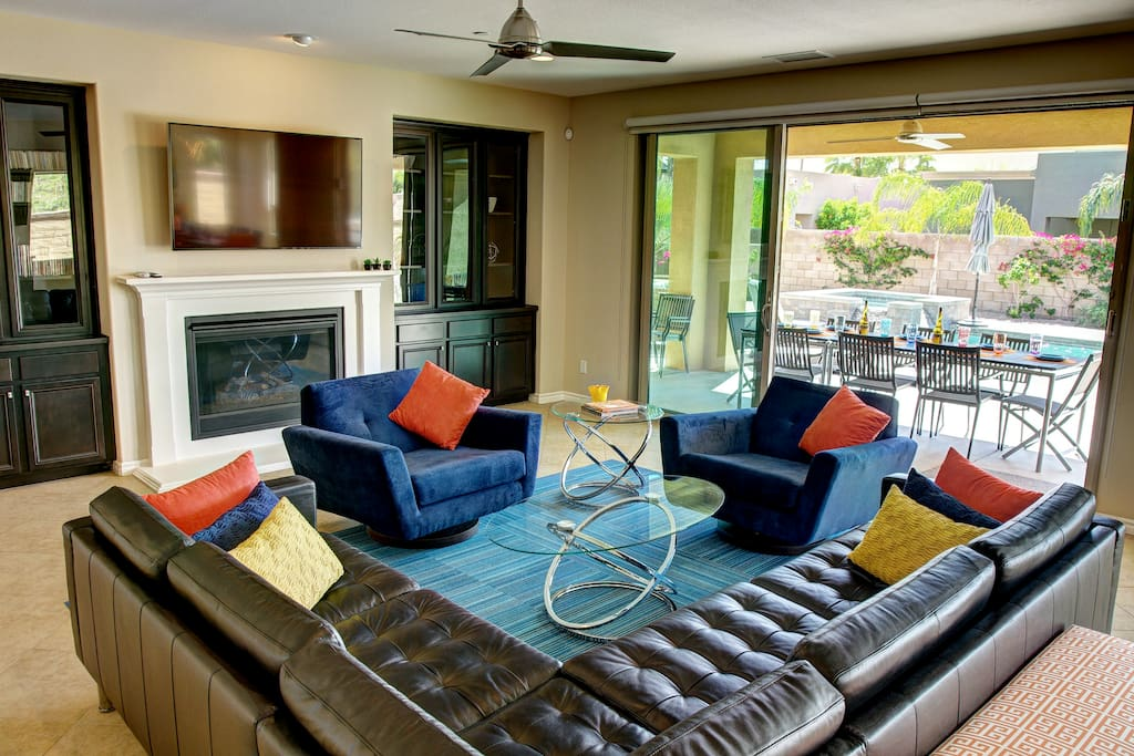 """Living room w/ fireplace and 60"""" TV. Opens to backyard."""