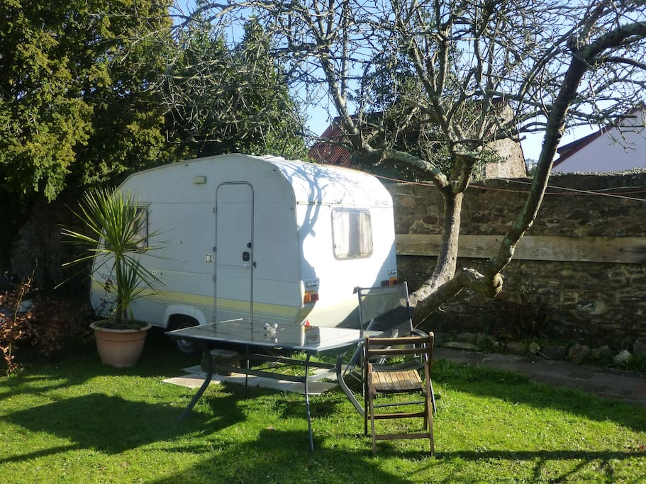 2/3 BERTH CARAVAN WITH TABLE AND CHAIRS OUTSIDE.