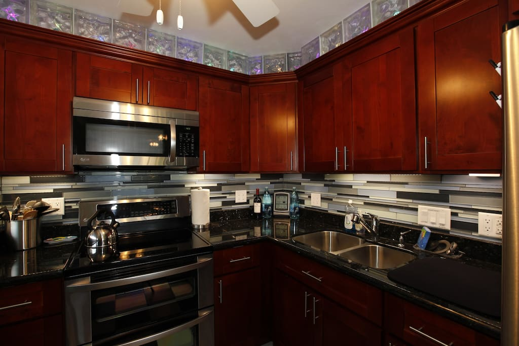 Dark Cherry Cabinetry, Granite Countertops, Under Cabinet Lighting, and Color Changing Glass Blocks!
