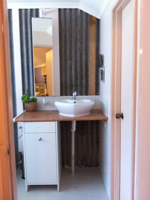 The ensuite features original tin cladding used on the dairy when it was built in the 50s. The shower is walk-in and spacious.