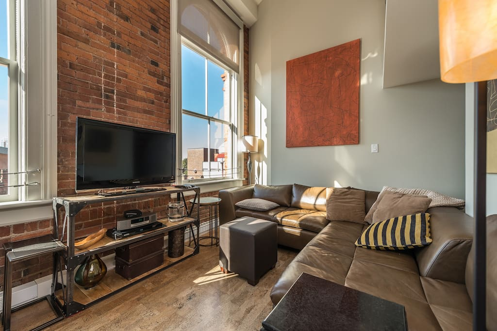 Living room with 13 foot ceilings and full height west facing windows