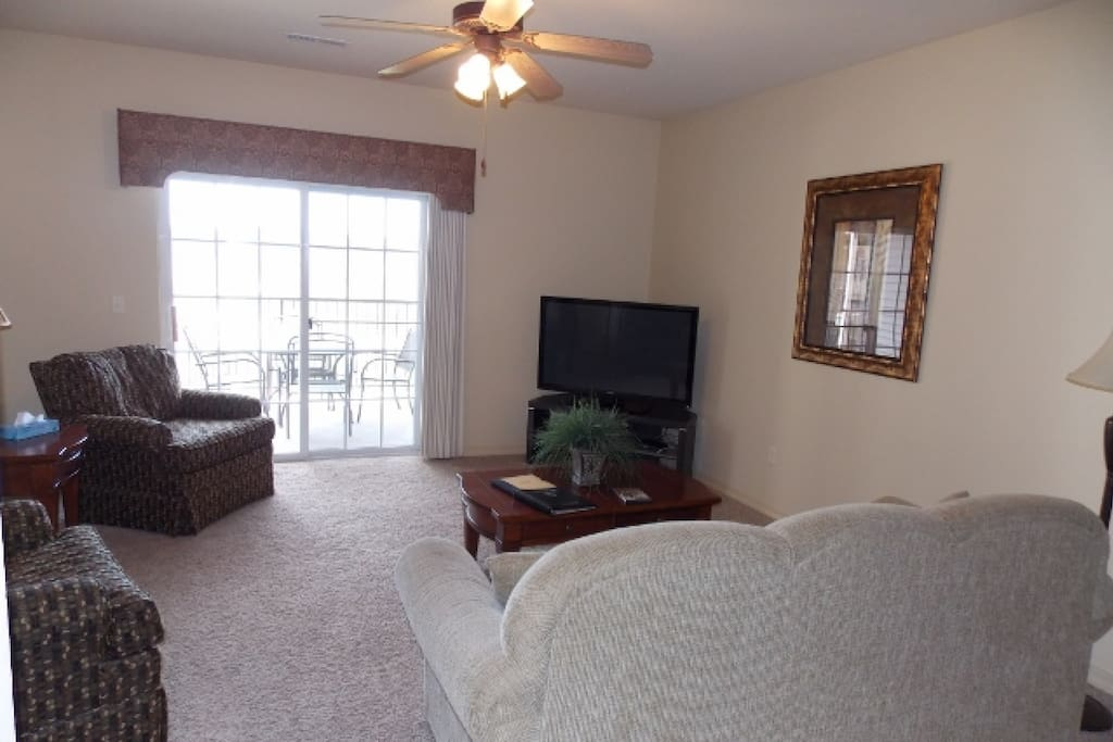 Living area with Large Flat Screen TV and View of Private Deck