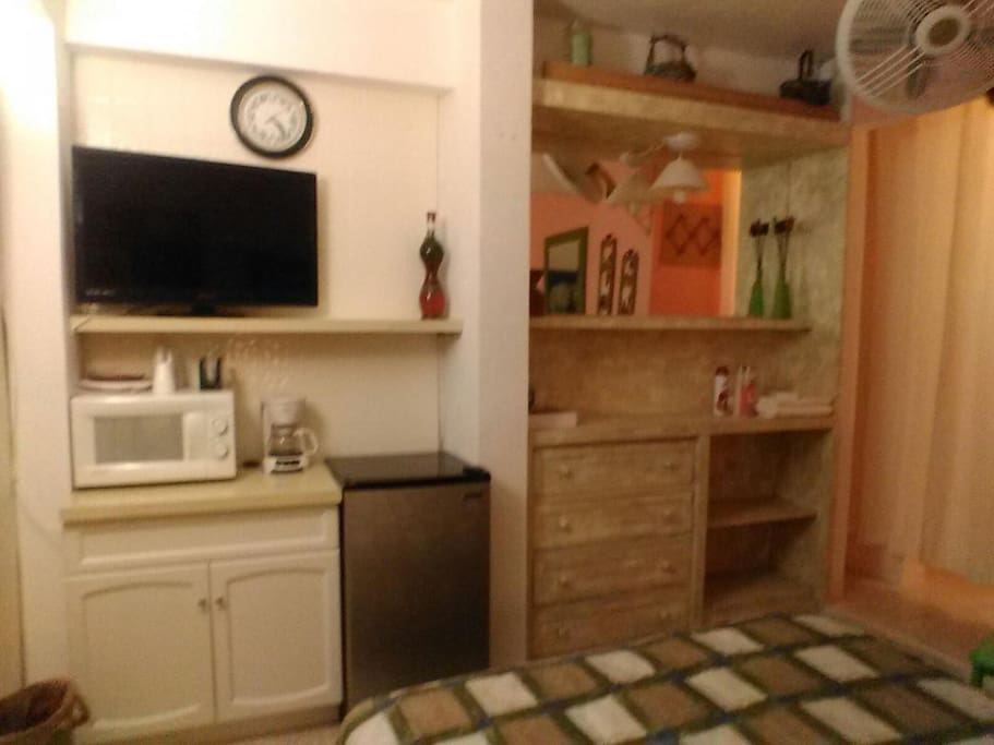 "32"" TV,  refrigerator and microwave in-room, with chest, shelves and fan, inside this mini studio sole room."