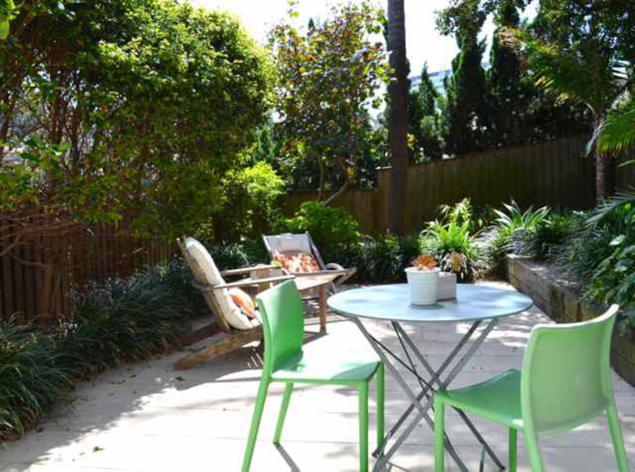 Private courtyard garden with table and chairs
