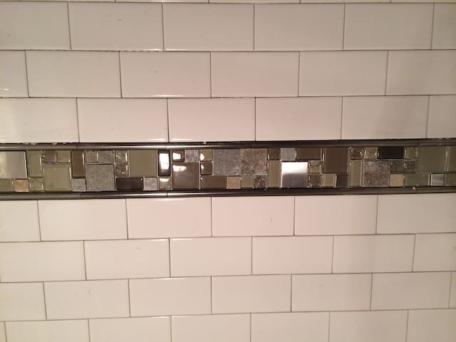 Subway tile; stone-and-glass border w/ pewter liners