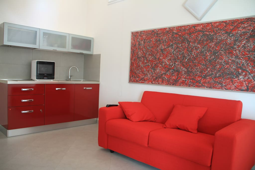 Angolo cottura attrezzato per ogni necessità e comodo divano letto