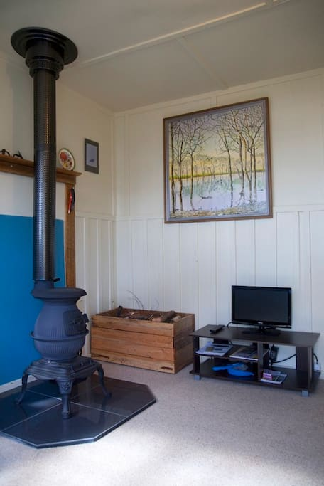 Pot bellied stove and entertainment table. 'Bush furniture' wood box. Paintings are originals.