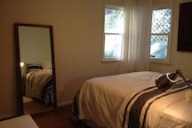Second bedroom with windows overlooking giant stock bamboo and olive trees.