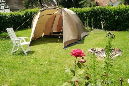 Zelt im Garten mit Lagerfeuer umgeben von Rosen - Schwanau