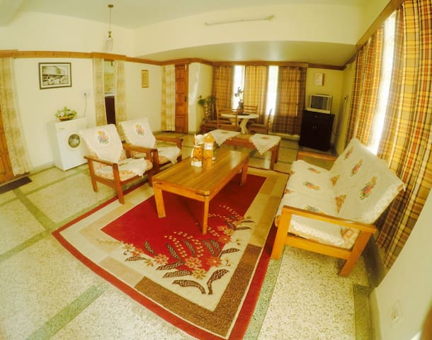 Spacious and comfortable living room equipped with TV , washer and other amenities.