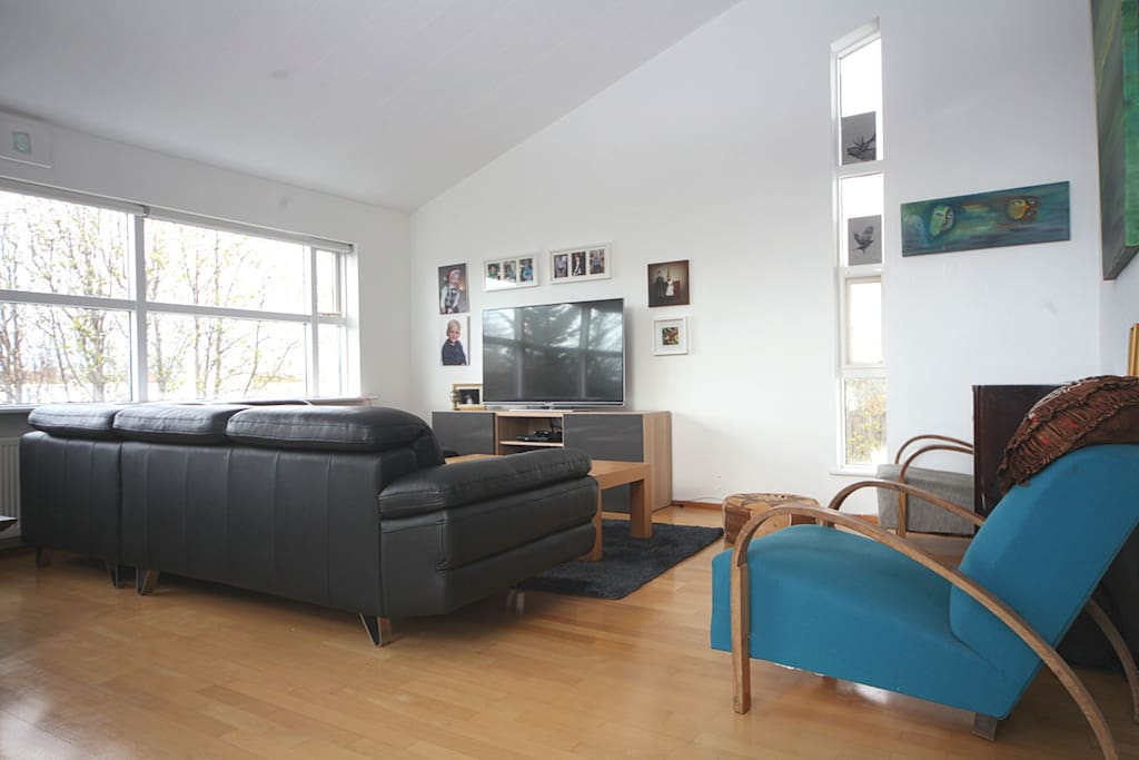Spacious livingroom with a large TV and many sofas and seating