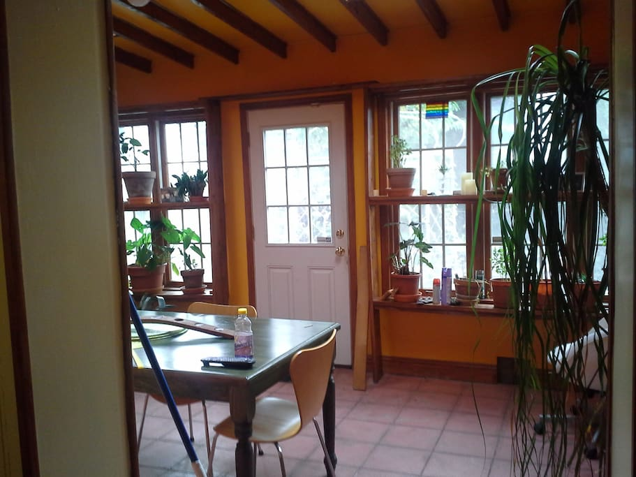 Sun room from kitchen. Comfortable dining and hanging out in the light. Skylights, herbs and plants galore. There is a tv hidden behind a plant that you can watch premium cable or just find out the weather before you leave for the day. Or play some music