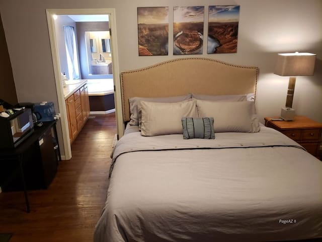 Comfortable living area with king sized Sleep Number bed, couch, table and chairs