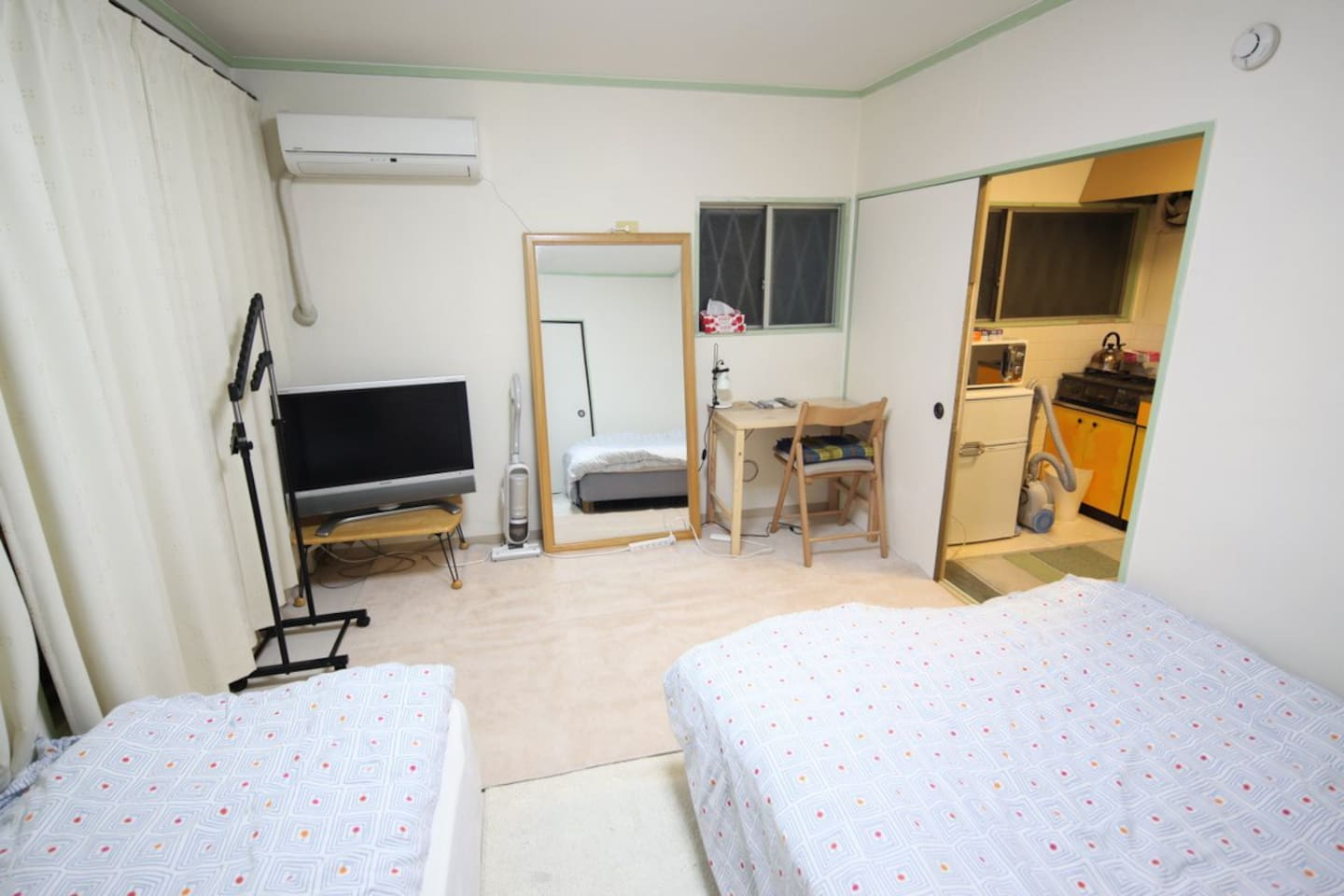 Bedroom with two beds and TV