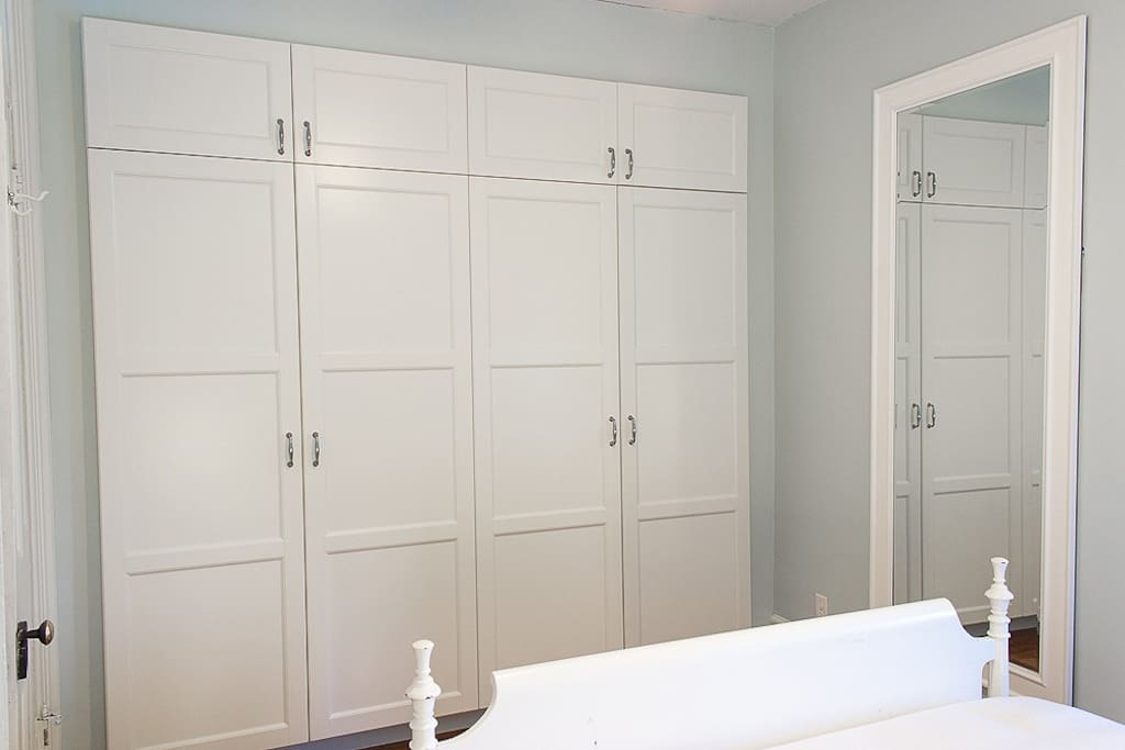 Ample storage space in the bedroom with these built-in wardrobes. An iron and ironing board are stored behind the door on the right-hand side of the wardrobe.