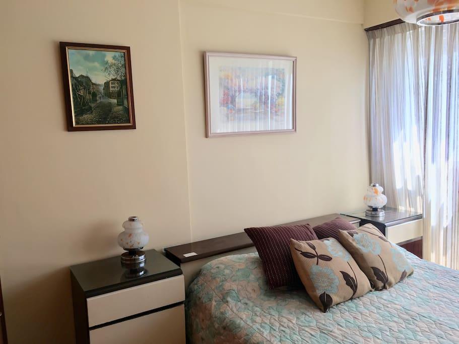 Dormitorio con cama matrimonial, y ventanal por donde entra el sol de la mañana
