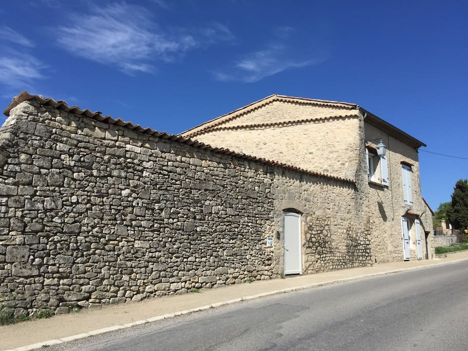 un haut mur de pierre qui protège terrasse et jardin des regards