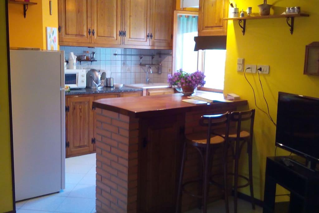 la cucina con bancone e 2 sgabelli