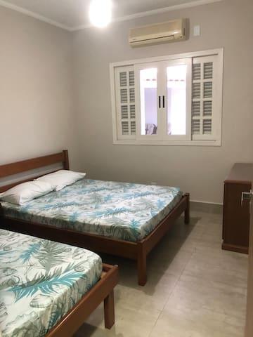 Quarto com cama de casal , solteiro ar condicionado , ventilador de teto e colchão extra .