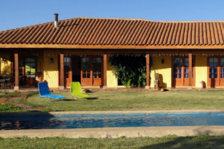 Hermosa casa con terraza y amplio corredor, piscina, jardines, rodeada de viñedos y cultivos.