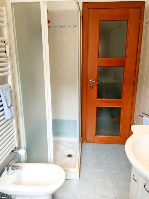 Bagno con doccia, bidet e lavatrice. Bathroom with shower and washing machine.