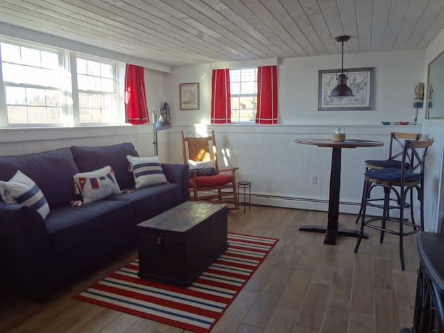 Spacious living room with close up views of Wiscasset tidal bay, moored boats, and Castle Tucker.