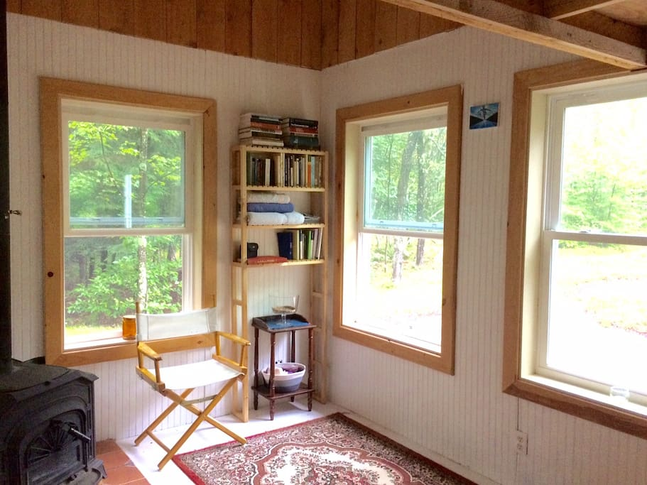 cozy wood stove, walls of windows, library and directors chair