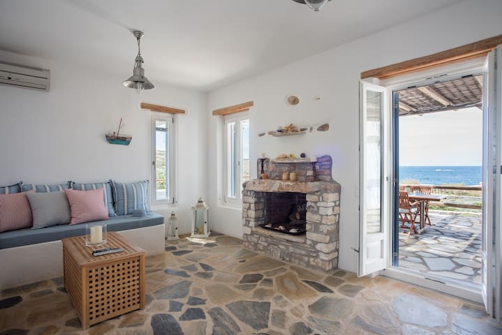 Spacious light living room with views of the blue Aegean sea.
