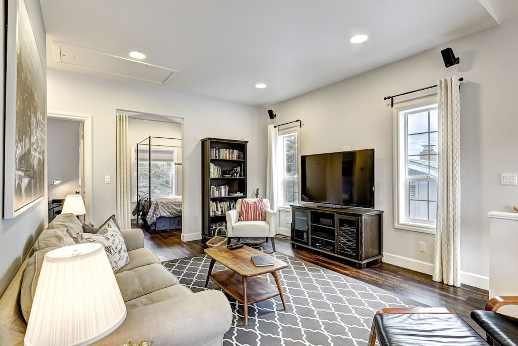 """Main room with 55"""" TV and surround sound. The books have been moved to the bedroom and there is now a sliding barn-style door to provide privacy for the bedroom"""