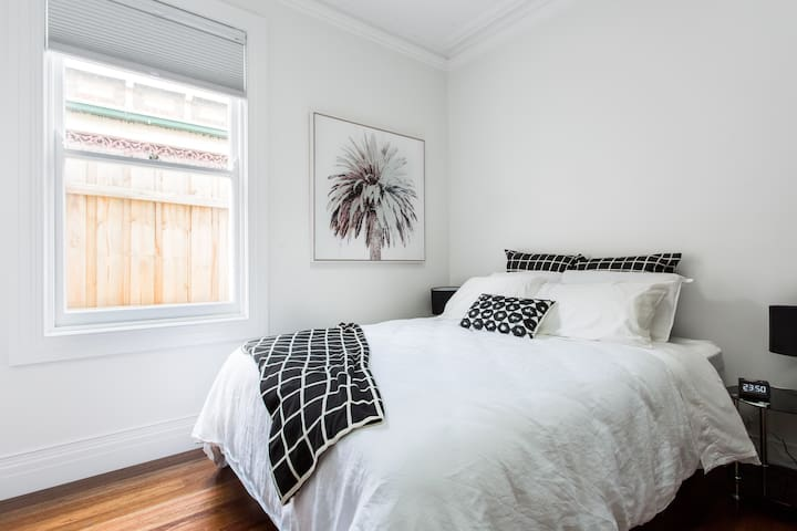 The second bedroom embraces a black and white colour scheme with a large window and ornate fireplace