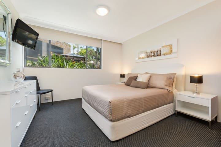 Large bedroom with queen bed, large wardrobe, TV
