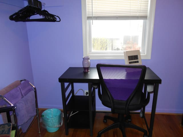 desk with shelves, purple back desk chair, matching towels, clock and vase