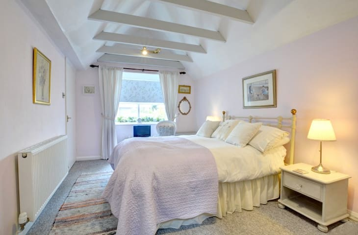Bedroom with  vaulted ceiling and beams.