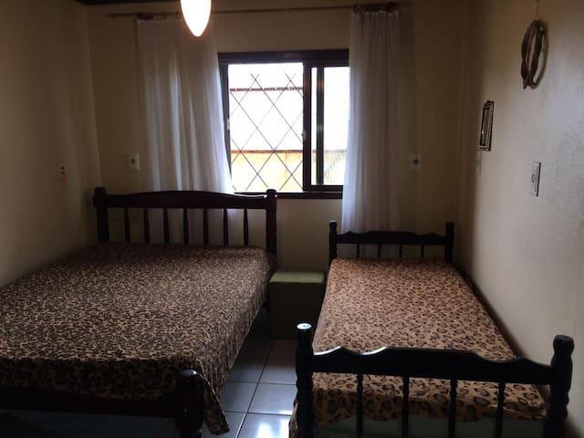 Quarto 2 com ventilador de teto e armário aberto para disposição de roupas e calçados.