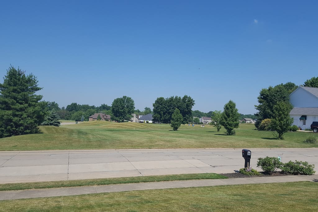 Front view of Golf course. You could walk right across the street and be at the clubhouse. Play some rounds of golf.