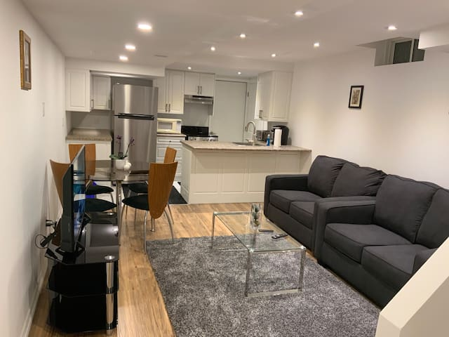 Living room with two sofa beds , dining table, chairs, TV and kitchen