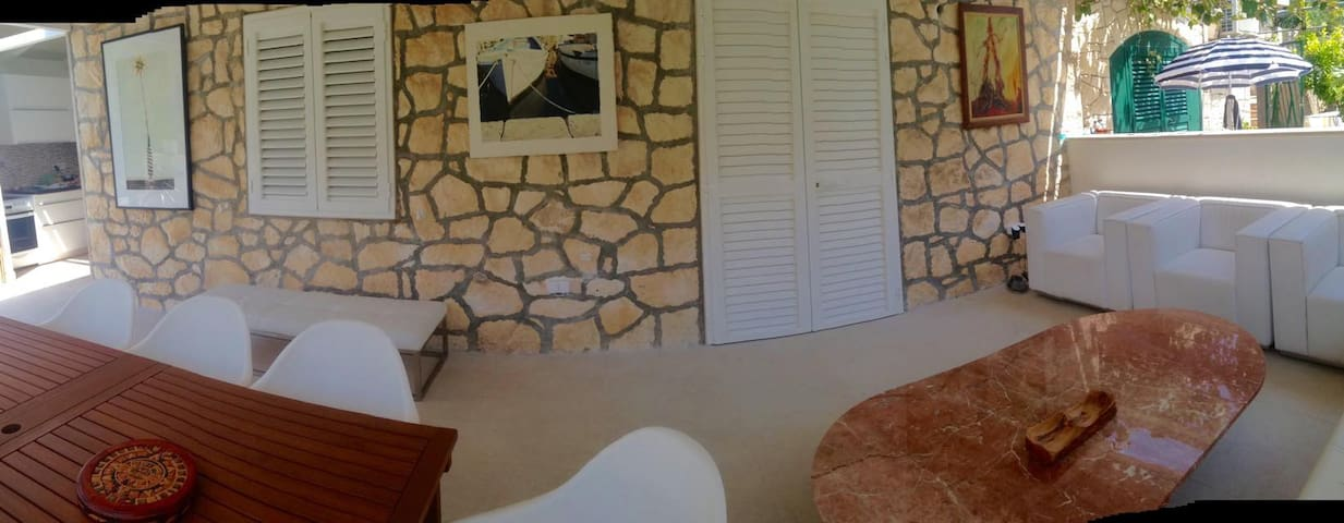 """Rent """"White Shade"""" a beautiful place in Bol Brac Croatia, beautiful place with the most famous beach Zlatni Rat.  Lux, well thermal isolated newly redone and refurnished (July 2017), ground floor modern flat - 3 bedrooms, 2 bathrooms + 1 outdoor shower,  2 separate entrances - convenient if 2 couples or families   Less then 100 m from the sea and Bol's center ... everything is within 1 minute walk).  New summer kitchen fully equipped with dishwasher and wine cooler. Washing machine is in the closet that is next to the open """"drying place""""  All made of top quality materials. EC in the """"TV room"""", each room has a sealing fan, """"terrace - living room"""" has 2 fans and the kitchen has 1 fan - totally 7 ceiling fans.  1 parking space - just next to the entrance gate. 1 adult bicycle and 2 kid's scooters available."""